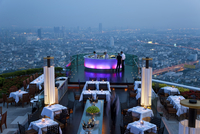 High angle view of rooftop restaurant on a skyscraper, illuminated cityscape in the distance. 11093023327| 写真素材・ストックフォト・画像・イラスト素材|アマナイメージズ