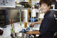 Waitress working in the kitchen of a Japanese sushi restaurant, smiling at camera. 11093023552| 写真素材・ストックフォト・画像・イラスト素材|アマナイメージズ