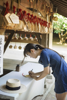 Young woman wearing blue dress writing on wooden fortune telling plaque at Shinto Sakurai Shrine, Fukuoka, Japan. 11093023577| 写真素材・ストックフォト・画像・イラスト素材|アマナイメージズ