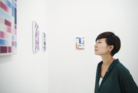 Woman with short black hair wearing green shirt standing in art gallery, looking at modern painting. 11093023625| 写真素材・ストックフォト・画像・イラスト素材|アマナイメージズ