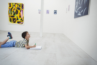 Boy with short black hair lying on floor in art gallery with pen and paper, looking at modern painting. 11093023626| 写真素材・ストックフォト・画像・イラスト素材|アマナイメージズ