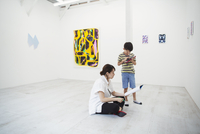 Woman with black hair wearing white shirt sitting on floor in art gallery with pen and paper, boy standing beside her. 11093023629| 写真素材・ストックフォト・画像・イラスト素材|アマナイメージズ