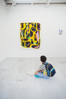 Boy with short black hair wearing backpack sitting on floor in art gallery with pen and paper, looking at modern painting. 11093023636| 写真素材・ストックフォト・画像・イラスト素材|アマナイメージズ
