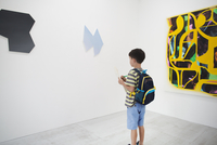 Boy with short black hair wearing backpack standing in art gallery, holding pen and paper, looking at modern painting. 11093023637| 写真素材・ストックフォト・画像・イラスト素材|アマナイメージズ