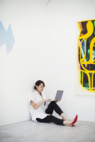 Woman with short black hair wearing white shirt, black trousers and red high heel shoes sitting on floor i art gallery, holding 11093023648| 写真素材・ストックフォト・画像・イラスト素材|アマナイメージズ