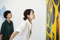 Two women standing in an art gallery, looking at an abstract modern painting. 11093023653| 写真素材・ストックフォト・画像・イラスト素材|アマナイメージズ