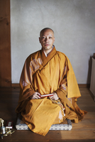 Buddhist monk with shaved head wearing golden robe kneeling on floor in a temple, holding mala, looking at camera. 11093023751| 写真素材・ストックフォト・画像・イラスト素材|アマナイメージズ