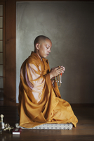 Side view of Buddhist monk with shaved head wearing golden robe kneeling indoors in a temple, holding mala, praying. 11093023753| 写真素材・ストックフォト・画像・イラスト素材|アマナイメージズ
