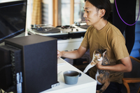 Man sitting at a desk in front of computer, calico cat with white, brown and black fur on his lap. 11093023789| 写真素材・ストックフォト・画像・イラスト素材|アマナイメージズ
