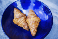 High angle close up of two freshly baked croissants on a blue plate. 11093023861| 写真素材・ストックフォト・画像・イラスト素材|アマナイメージズ