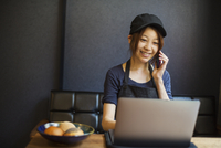 Woman working in a bakery, wearing baseball cap, sitting at table in front of laptop, using mobile phone. 11093023863| 写真素材・ストックフォト・画像・イラスト素材|アマナイメージズ