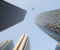 Low angle view from urban street towards clear sky, along glass and steel facades of tall skyscrapers, passenger plane going pas 11093025037| 写真素材・ストックフォト・画像・イラスト素材|アマナイメージズ