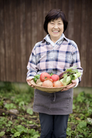 Woman with black hair wearing checkered shirt standing in a garden, holding basket with fresh vegetables, smiling at camera. 11093025180| 写真素材・ストックフォト・画像・イラスト素材|アマナイメージズ