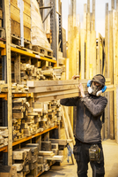 Man wearing ear protectors and dust mask standing in a warehouse, carrying long planks of wood on his shoulder. 11093025530| 写真素材・ストックフォト・画像・イラスト素材|アマナイメージズ