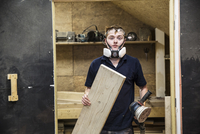 Young man wearing dust mask and protective goggles standing in a workshop, holding sander piece of wood. 11093025549| 写真素材・ストックフォト・画像・イラスト素材|アマナイメージズ