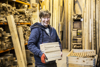 Smiling blond woman wearing work gloves standing in a workshop, holding stack of wood, looking at camera. 11093025551| 写真素材・ストックフォト・画像・イラスト素材|アマナイメージズ