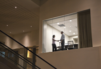 A view looking into a conference room at night with two business people at work at a conference table. 11093026717| 写真素材・ストックフォト・画像・イラスト素材|アマナイメージズ