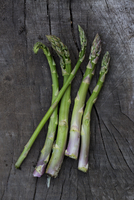 Close up of freshly harvested asparagus on dark grey wood.