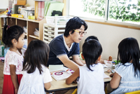 Male teacher talking to group of children at a table n a Japanese preschool.