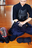 Male Japanese Kendo fighter kneeling on wooden floor, putting on Kote, hand protectors.