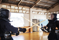Two Japanese Kendo fighters wearing Kendo masks practicing with wood sword in gym.