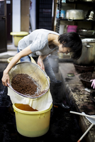 Japanese woman standing in a textile plant dye workshop, pouring plant dye from a sieve into a yellow bucket.. 11093027704| 写真素材・ストックフォト・画像・イラスト素材|アマナイメージズ