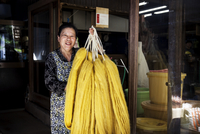 Japanese woman working in a plant dye workshop,  holding up freshly dyed bright yellow fabric. 11093027710| 写真素材・ストックフォト・画像・イラスト素材|アマナイメージズ