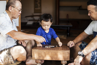 Two Japanese men and little boy sitting on floor on porch of traditional Japanese house, playing Go. 11093027793| 写真素材・ストックフォト・画像・イラスト素材|アマナイメージズ