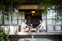 Two Japanese men and little boy sitting on floor on porch of traditional Japanese house, playing Go. 11093027794| 写真素材・ストックフォト・画像・イラスト素材|アマナイメージズ