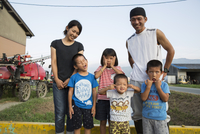 Portrait of smiling Japanese farmer, his wife and four children standing in their yard, children pulling faces at camera.
