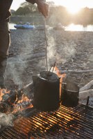 A man checks a pot of coffee on a rack over a campfire on a river camping trip
