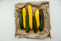 Yellow and green courgettes displayed on a crumpled brown paper bag.