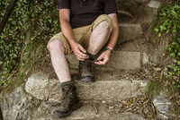 A man sitting tying up his walking boots laces on a stone step.