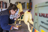 Woman standing in workshop, painting a traditional wooden carousel horse from merry-go-round. 11093030003| 写真素材・ストックフォト・画像・イラスト素材|アマナイメージズ