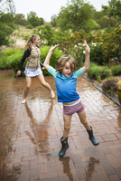 5 year old boy and his 13 year old sister dancing in the rain.