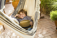 Portrait of six year old boy lying in hammock on porch
