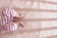 Baby girl lying in a cot, partial view 11094005800| 写真素材・ストックフォト・画像・イラスト素材|アマナイメージズ
