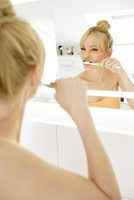 Woman looking at her mirror image while brushing teeth 11094010562| 写真素材・ストックフォト・画像・イラスト素材|アマナイメージズ