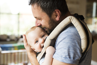 Happy father with baby in baby carrier at home 11094011933| 写真素材・ストックフォト・画像・イラスト素材|アマナイメージズ