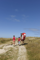 France, Bretagne, Landeda, Father with two sons walking in d 11094017446| 写真素材・ストックフォト・画像・イラスト素材|アマナイメージズ