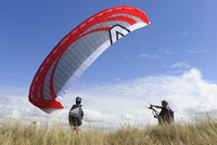 France, Bretagne, Landeda, Father and son with paraglider in 11094017447| 写真素材・ストックフォト・画像・イラスト素材|アマナイメージズ