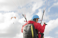 Paraglider up in the air in front of clouds 11094017965| 写真素材・ストックフォト・画像・イラスト素材|アマナイメージズ