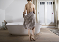 Naked woman with towel in front of modern bathtub 11094021760| 写真素材・ストックフォト・画像・イラスト素材|アマナイメージズ