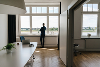 Businesswoman standing in modern office looking out of windo 11094025973| 写真素材・ストックフォト・画像・イラスト素材|アマナイメージズ