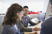 Salesman and couple finalizing paperwork in car dealership