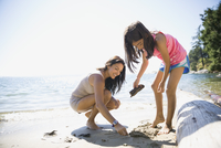Mother and daughter clam digging on sunny beach