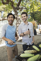 Smiling men drinking beer and barbecuing corn cobs 11096009604| 写真素材・ストックフォト・画像・イラスト素材|アマナイメージズ