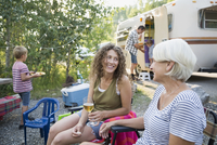 Mother and daughter drinking wine and talking campsite 11096013447| 写真素材・ストックフォト・画像・イラスト素材|アマナイメージズ