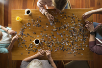 Overhead view family assembling jigsaw puzzle at table