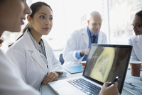 Doctors viewing x-ray on laptop in meeting 11096016437| 写真素材・ストックフォト・画像・イラスト素材|アマナイメージズ